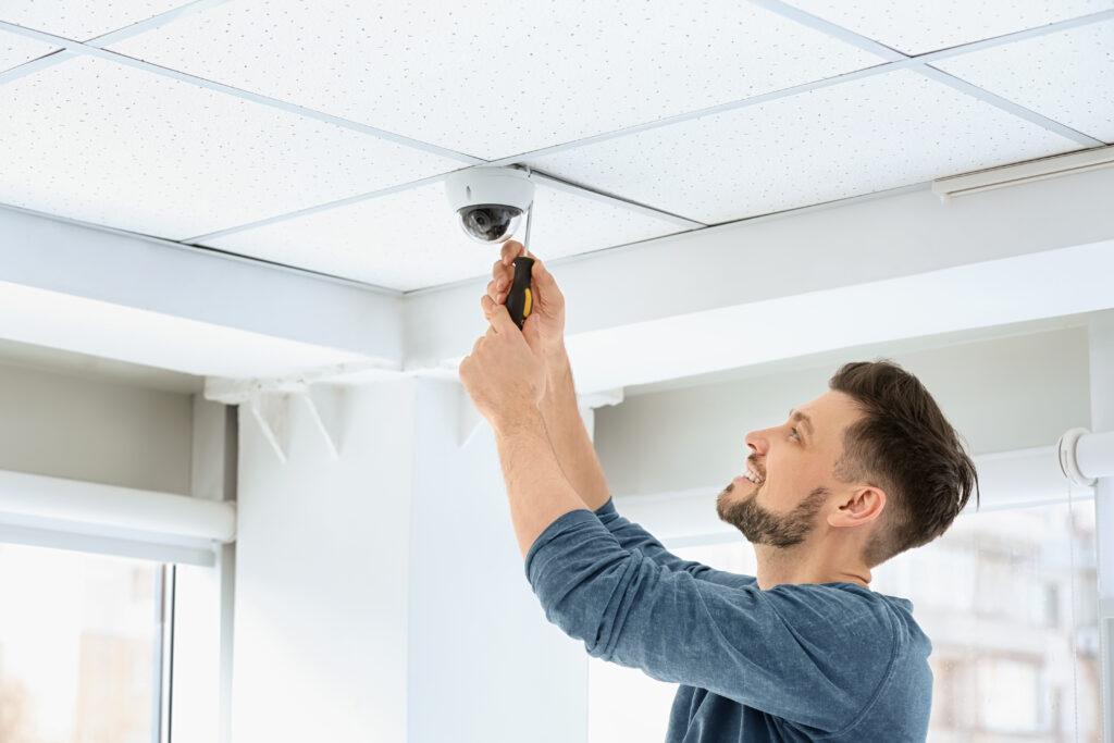 Handyman installing CCTV camera on ceiling